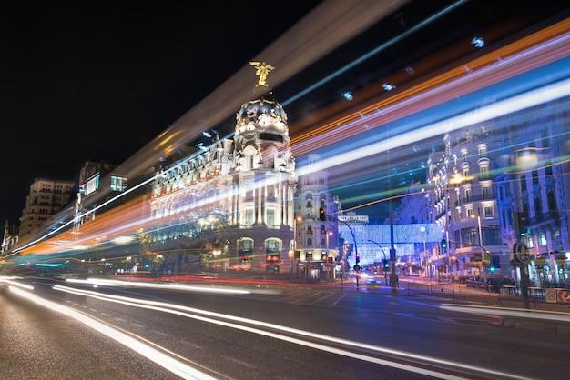Fotografia da noite da arquitectura da cidade de madrid, rua de gran via com raios do sinal. madri, espanha.