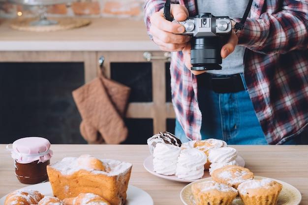 Fotografia de alimentos. variedade de sobremesas de pastelaria. homem com câmera tirando fotos de prato com merengue
