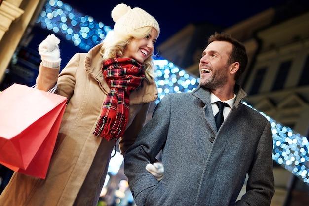 Fotografia de casal alegre com sacolas de compras