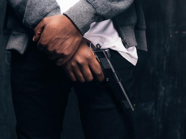 Fotografia de estúdio de gangster fechado preto armado irreconhecível