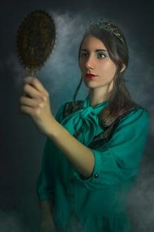 Fotografia de estúdio de uma menina com uma coroa, olhando no espelho.