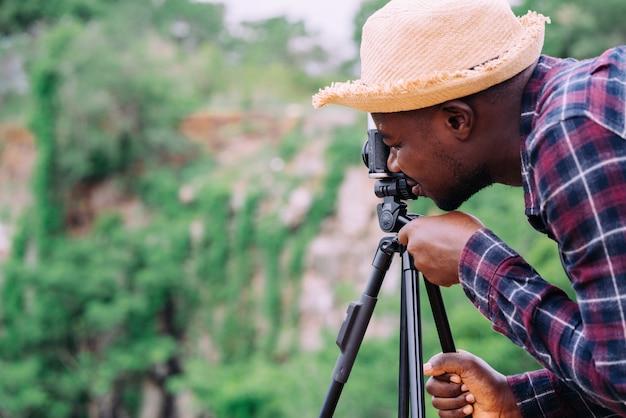 Fotografia de homem africano tirando a câmera com pé de tripé