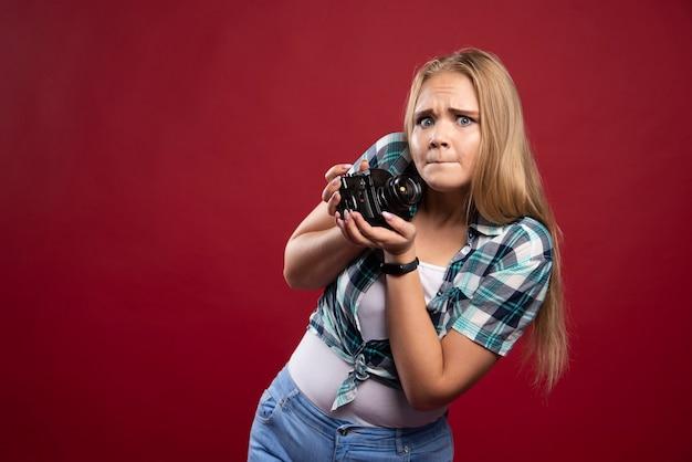 Fotografia de jovem loira segurando uma câmera profissional e não sabe como usá-la.