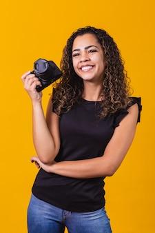 Fotografia de jovem mulher afro em fundo amarelo, segurando uma câmera fotográfica. vertical