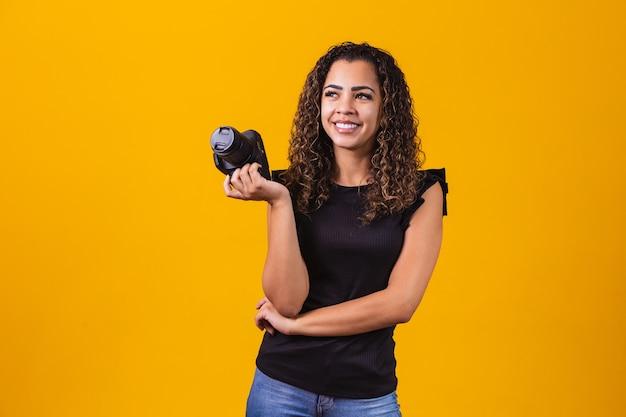 Fotografia de jovem mulher afro em fundo amarelo, segurando uma câmera fotográfica.