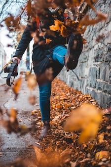 Fotografia de lapso de tempo de mulher chutando folhas do chão