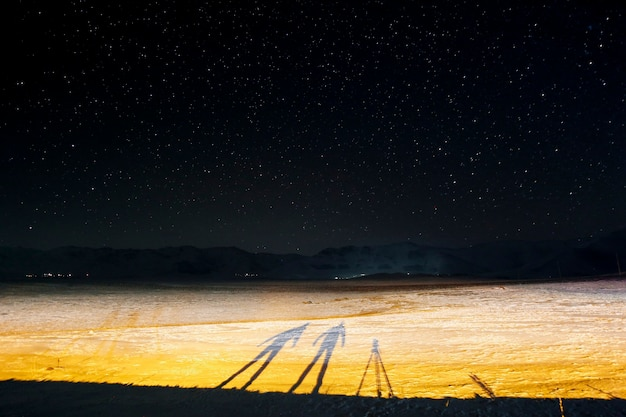 Fotografia de longa exposição. uma foto noturna e as silhuetas de dois fotógrafos à noite no inverno