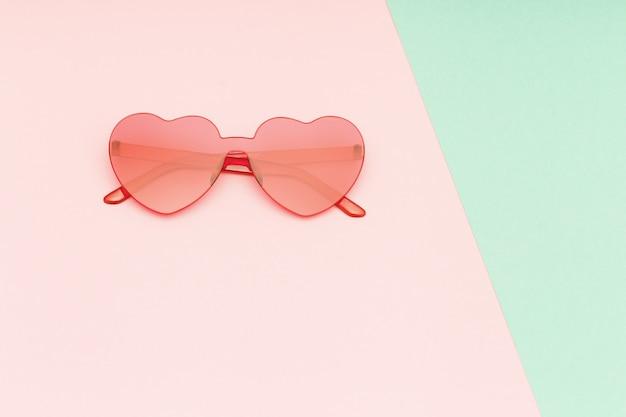 Fotografia de moda estilo minimalista com óculos em forma de coração sobre fundo verde e rosa de papel. óculos de sol modernos. conceito de verão na moda. copie o espaço.
