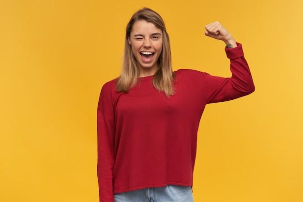 Fotografia de mulher jovem e forte e sorridente loira pisca o olho esquerdo, mostrando seus músculos, seu poder, mantém uma mão levantada dobrada e segurando um punho cerrado