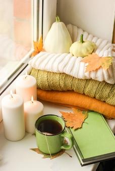 Fotografia de objetos de outono em um parapeito de janela em um apartamento com uma xícara de chá, folhas amarelas e velas
