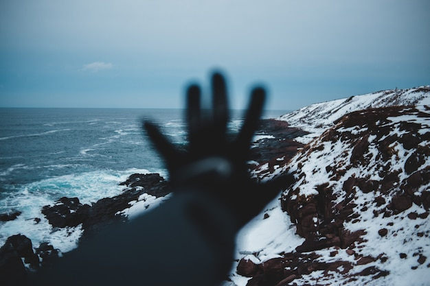 Fotografia de paisagem do penhasco coberto de neve, vendo o corpo de água