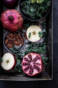 Fotografia de romã fresca com maçãs e nozes pecãs