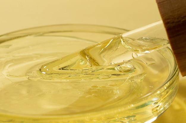 Fotografia do close up da pipeta de vidro com óleo na placa de petri.