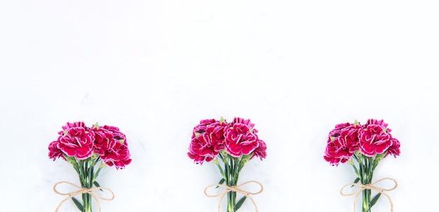 Fotografia do dia das mães de maio - lindo bando de cravos em flor amarrado por um laço isolado em uma mesa moderna e brilhante, copie o espaço, lay-out plana, vista superior, em branco para texto