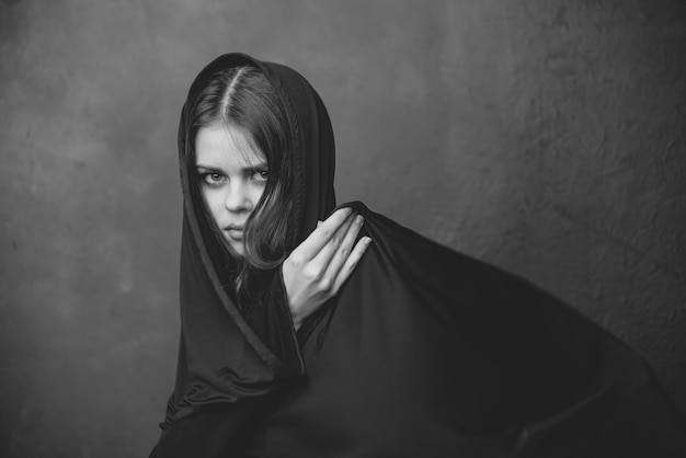 Fotografia em preto e branco de uma jovem com um pano na cabeça e um close-up cortado