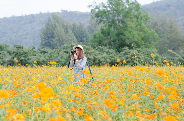 Fotografia feminina com câmera tirando uma foto da flor de calêndula