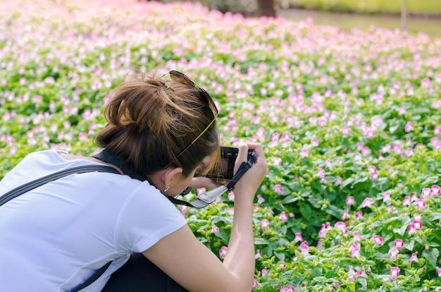 Fotografia feminina com câmera tirando uma foto de flor