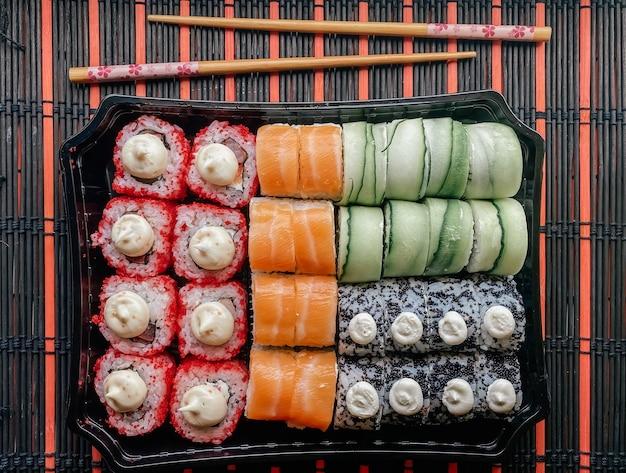 Fotografia flatlay de rolo colocado sobre uma mesa com pauzinhos para sushi. entrega em domicílio, rolos de sushi japoneses.