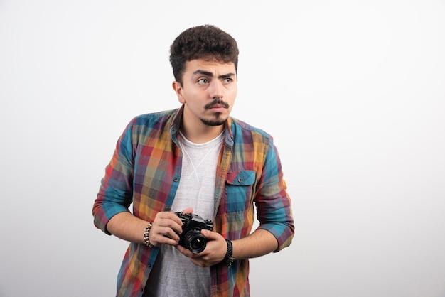 Fotografia jovem experiente em tirar fotos profissionais de maneira séria.