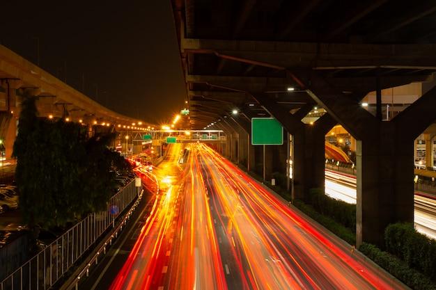 Fotografia longa da exposição que mostra o tracffic claro na estrada na cidade.