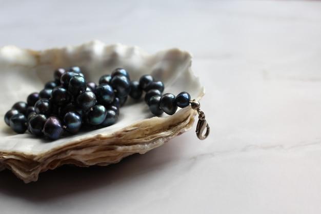 Fotografia macro de contas de pérola negra com pedras preciosas em uma concha