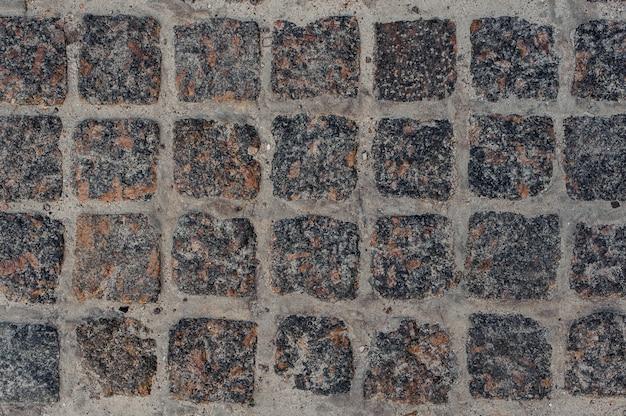 Fotografia macro do pavimento de estrada de bloco de pedra cinza