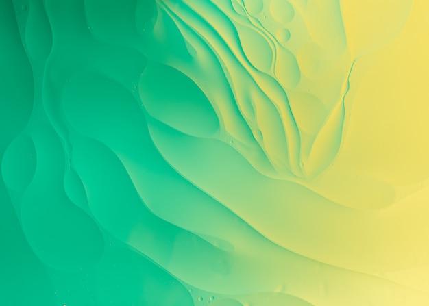 Fotografia macro óleo sobre água de fundo gradiente de cor verde e amarelo abstrato