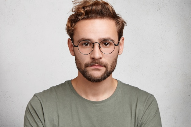 Fotografia na cabeça de um homem barbudo sério com bigode e barba, usando óculos redondos