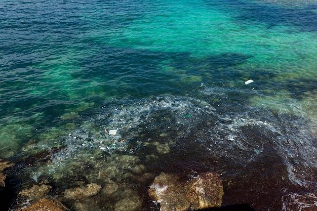 Fotografia observando a poluição do mar, afetando o meio ambiente marinho. resíduos de plástico e vários detritos