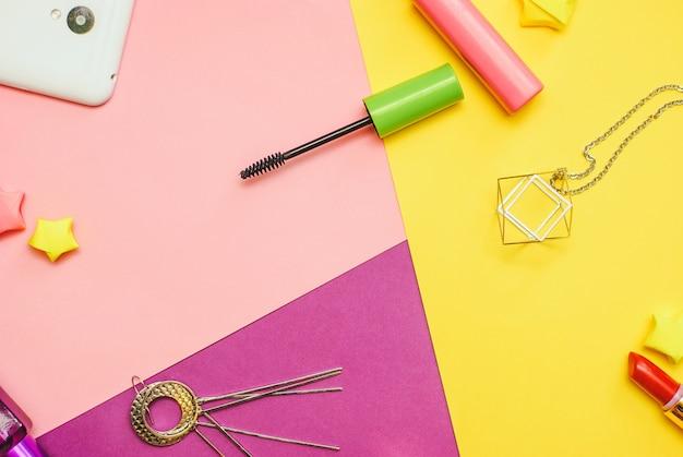 Fotografia plana leiga com cosméticos e acessórios em fundo colorido