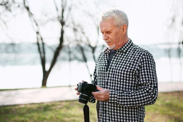 Fotografia real. homem sênior concentrado olhando para baixo e usando a câmera