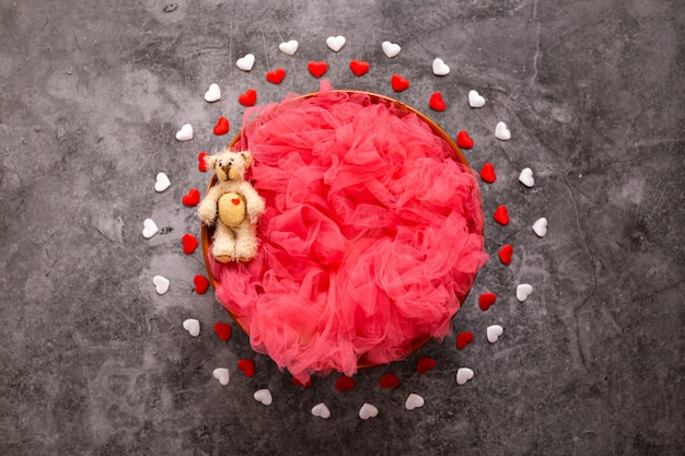 Fotografia recém-nascida digital para um dia dos namorados, corações vermelhos e brancos e uma tigela