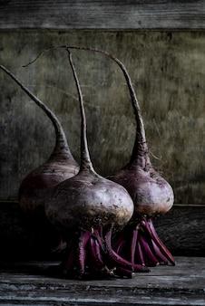 Fotografia vertical da natureza morta de três beterrabas - perfeita para um artigo sobre agricultura