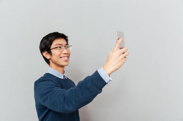 Fotografias de homem asiático ao telefone. selfie