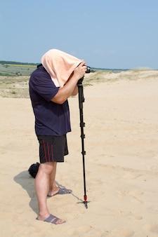 Fotógrafo adulto masculino com uma toalha na cabeça do calor está tirando fotos com uma câmera em um posto no deserto