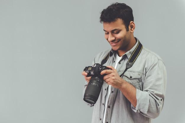 Fotógrafo afro-americano está usando sua câmera.