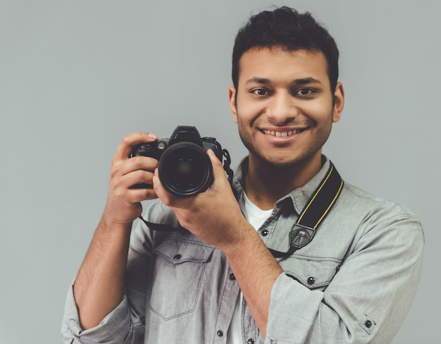 Fotógrafo afro está posando com sua câmera