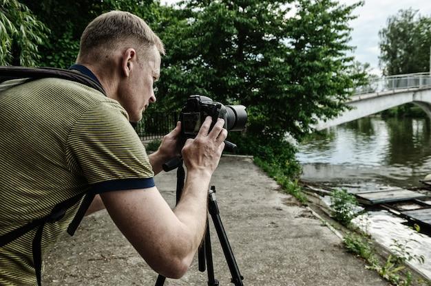 Fotógrafo, ajustando a câmera no tripé