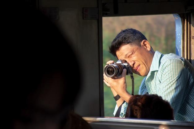 Fotógrafo asiático com câmera tirar fotos da janela aberta do trem vintage