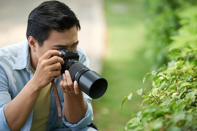 Fotógrafo asiático tirando fotos macro de folhas verdes