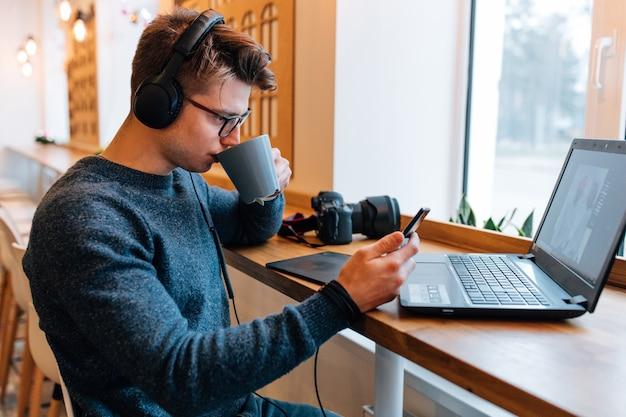 Fotógrafo bonito beber uma xícara de chá no café, olha para o telefone móvel