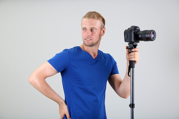 Fotógrafo bonito com câmera em monopé, em fundo cinza
