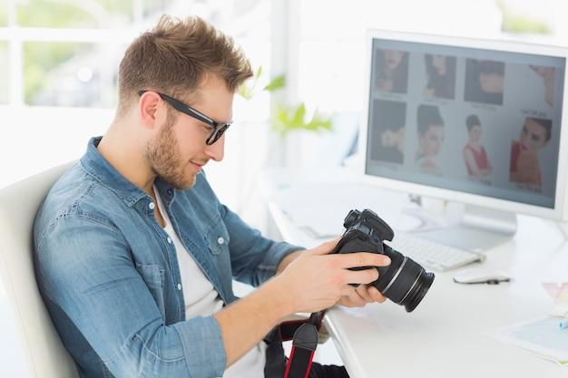 Fotógrafo bonito olhando para sua câmera