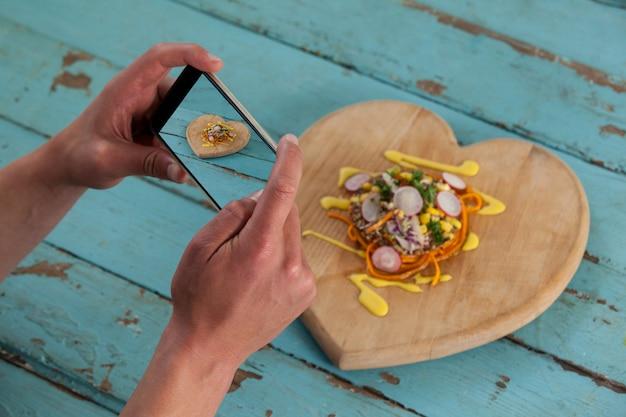 Fotógrafo, clicando em uma imagem de comida usando smartphone