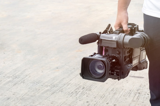 Fotógrafo, cobrindo um evento no exterior com uma câmera de vídeo
