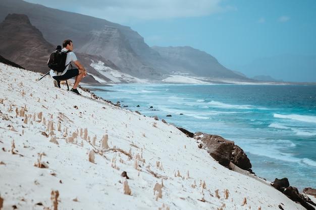 Fotógrafo com câmera, apreciando a cena costeira de dunas de areia. são vicente, cabo verde.