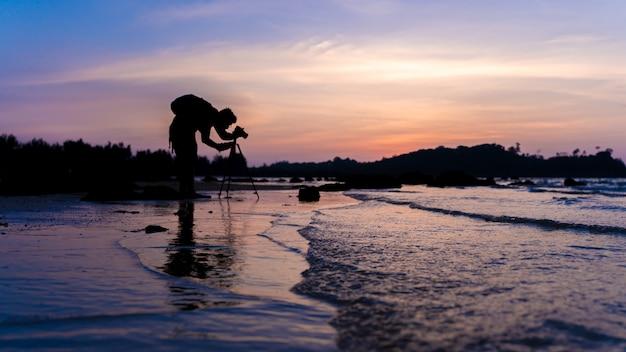 Fotógrafo com câmera digital e vista para o mar