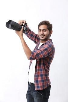 Fotógrafo com câmera na parede branca