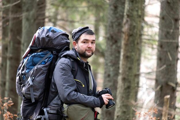 Fotógrafo com mochila de caminhada tirando fotos da natureza com câmera fotográfica digital.