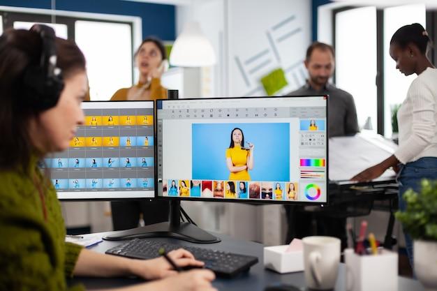 Fotógrafo criativo usando programa de retoque digital, usando fone de ouvido para edição de fotos para o cliente